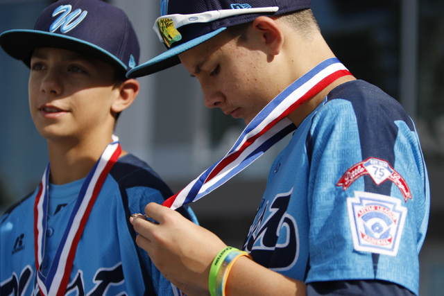 Mountain Ridge Little League player Andrew Matulich (14), right, looks at his medal as he stands during a ceremony to honor his team for their Little League World Series performance at Las Vegas C ...