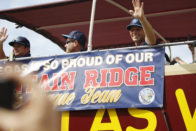Mountain Ridge Little League manager Ashton Cave, right, waves as his team leaves on a bus for their parade following a ceremony honoring them for their Little League World Series performance at L ...