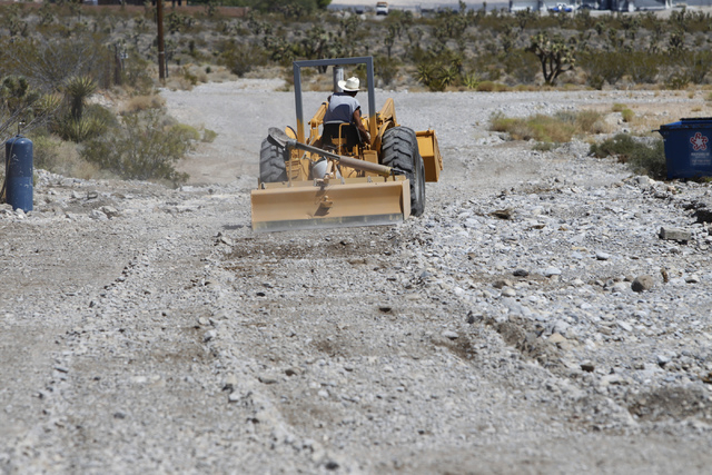Stu Cook uses his tractor for leveling out the gravel road near his home at the intersection of Barr Road and Lauri Lane at Lower Kyle Canyon Thursday, Aug. 7, 2014. (Erik Verduzco/Las Vegas Revie ...