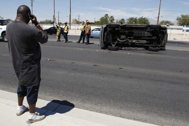 Andre Jacobs, left, makes a call after being involved in a car accident where his car flipped on its side on Lake Mead Boulevard near Tonopah Drive in Las Vegas Friday, Aug. 29, 2014. (Erik Verduz ...