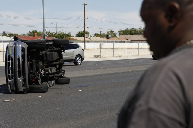 Andre Jacobs waits in front of his car after being involved in a car accident on Lake Mead Boulevard near Tonopah Drive in Las Vegas Friday, Aug. 29, 2014. Jacobs said he flipped his car after he  ...