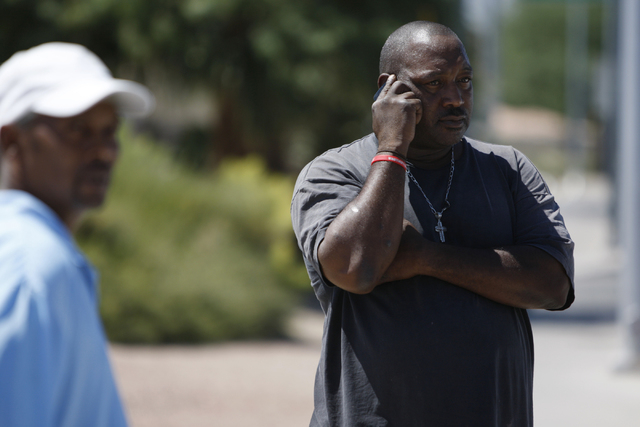Andre Jacobs, right, makes a call after being involved in a car accident where his car flipped on its side on Lake Mead Boulevard near Tonopah Drive in Las Vegas Friday, Aug. 29, 2014. (Erik Verdu ...