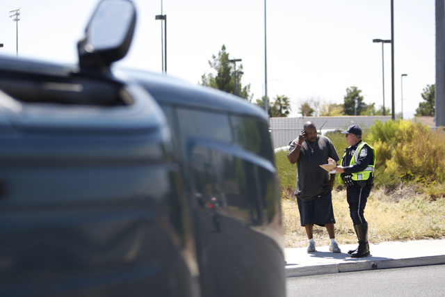 Andre Jacobs, left, is interviewed for a police statement after being involved in car accident on Lake Mead Boulevard near Tonopah Drive in Las Vegas Friday, Aug. 29, 2014. (Erik Verduzco/Las Vega ...