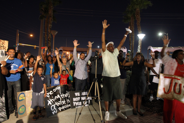People hold their hands up during a peace rally and vigil for Michael Brown at the Martin Luther King Jr. statue on the corner of North Martin Luther King Boulevard and West Carey Avenue in North  ...