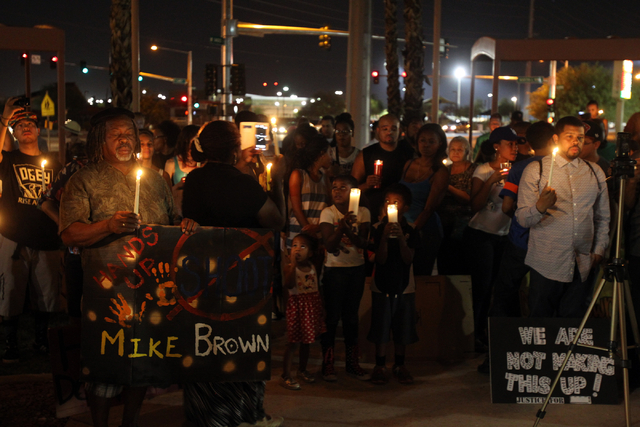 People listen as names of those killed at the hands of police are read during a peace rally and vigil for Michael Brown at the Martin Luther King Jr. statue on the corner of North Martin Luther Ki ...