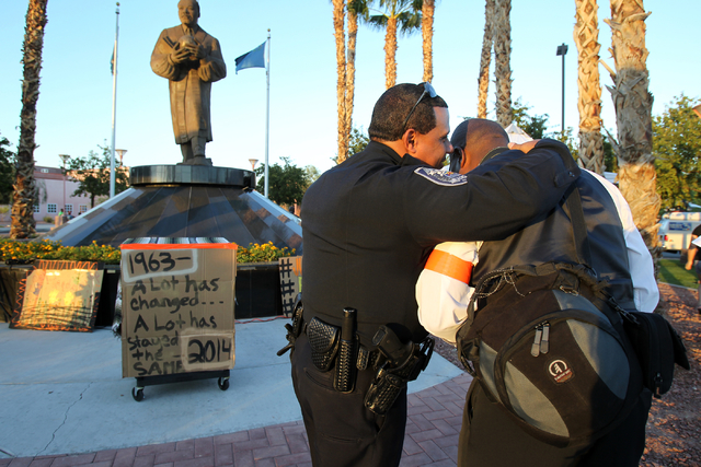 North Las Vegas Police Lt. Wilson Crespo, left, and organizer Rodney Smith talk before a peace rally and vigil for Michael Brown at the Martin Luther King Jr. statue on the corner of North Martin  ...