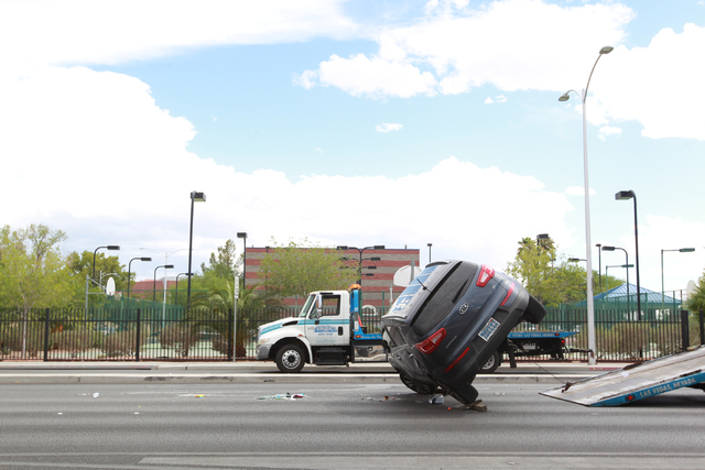 A towing crew flips over a vehicle that was involved in a rollover crash also involving a sedan, not pictured, at Martin Luther King Boulevard and Washington Avenue in Las Vegas on Wednesday, Aug. ...