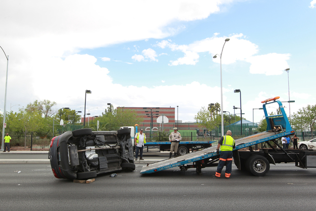 Las Vegas police and a towing crew respond to a two vehicle crash where one rolled over at Martin Luther King Boulevard and Washington Avenue in Las Vegas on Wednesday, Aug. 20, 2014. (Chase Steve ...