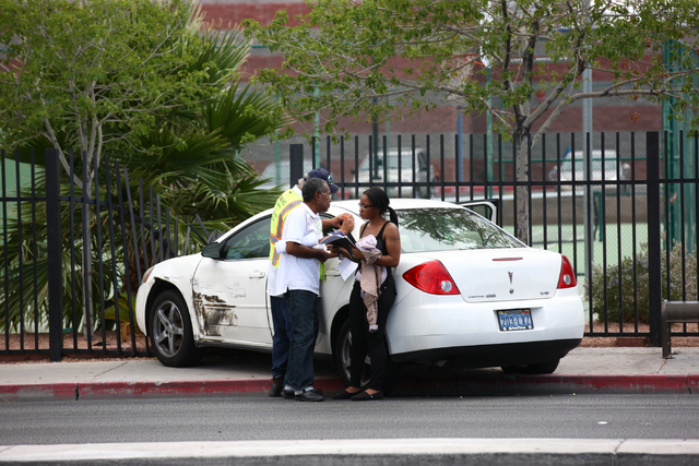 People are seen by a sedan that was involved in a two vehicle crash where one rolled over at Martin Luther King Boulevard and Washington Avenue in Las Vegas on Wednesday, Aug. 20, 2014. (Chase Ste ...