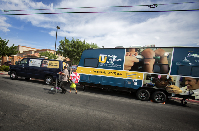 People walk pass the Touro University Nevada Mobile Healthcare Clinic in the homeless corridor on Foremaster Lane on Wednesday, Aug.13, 2014. Touro recently begin providing mobile healthcare to th ...