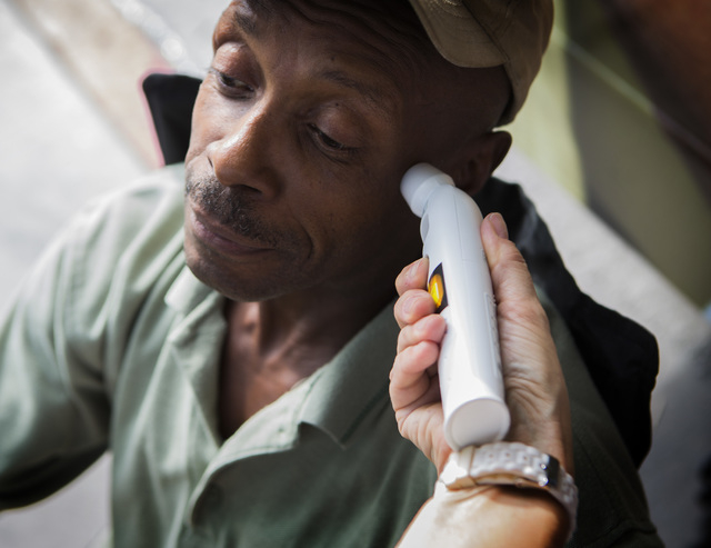 Kirk Haynes gets his temperature checked at the Touro University Nevada Mobile Healthcare clinic  during a  medical examination in the homeless corridor on Foremaster Street on Wednesday, Aug.13,  ...
