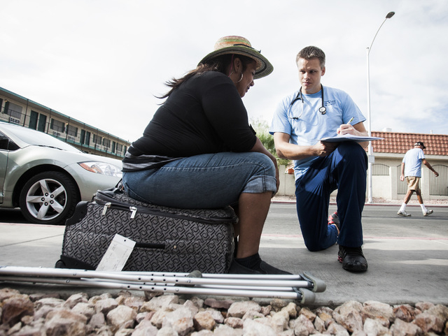 Clayton Halford, right, a physician assistant student at Touro University Nevada, asks Vicky Vinlicheenie medical questions in the homeless corridor on Foremaster Lane on Wednesday, Aug.13, 2014.  ...