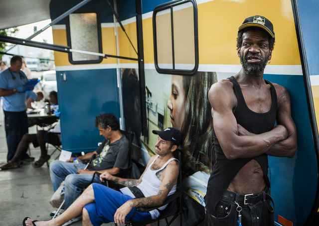 Rico James, right, waits for treatment at the Touro University Nevada Mobile Healthcare clinic in the homeless corridor on Foremaster Lane on Wednesday, Aug.13, 2014. He has a growth on his neck t ...