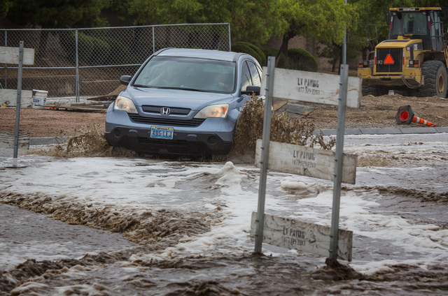 A vehicle maneuvers the  flooded Grand Teton Drive in northwest Las Vegas on Monday, Aug. 4, 2014. Overnight monsoon rains caused flooding in the area. (Jeff Scheid/Las Vegas Review-Journal)