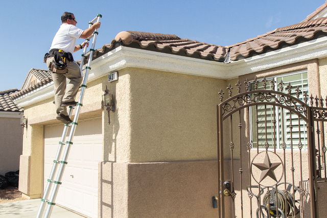 WIN Home Inspection inspector Andrew Lyman checks the condition of a Las Vegas house on Friday, July 18, 2014. The median price of single-family homes in Las Vegas hit $200,000 in July. (Jenna Dos ...