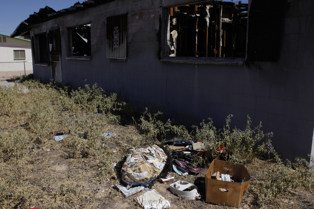 Trash is seen on the front yard of a burned down home at 2116 Carver Ave. in North Las Vegas Friday, Aug. 29, 2014. North Las Vegas officials plan to demolish arson-plagued homes as part of a city ...
