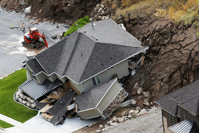 A home is damaged by a mudslide, Tuesday, Aug. 5, 2014 in North Salt Lake, Utah.  The home crumbled after rain-saturated soil from the hill above started piling up behind it at around 6 a.m. Tuesd ...