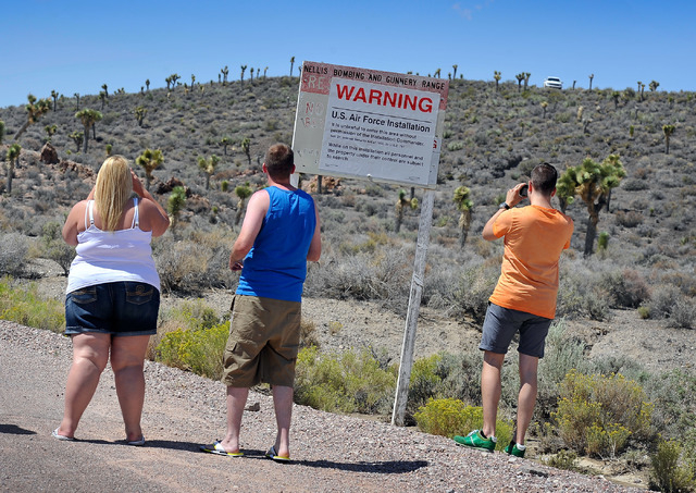 Under the watchful eye of security guards parked on the hill top, tourists, from left, Becky Cooper and Shane Cooper of England and Floris Otten of the Netherlands, visit the perimeter of Area 51  ...