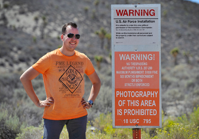 Floris Otten, of The Netherlands, stands by a warning sign as he poses for a photograph at the perimeter of the well guarded military installation on Tuesday, Aug. 5, 2014. Otten was a part of a s ...
