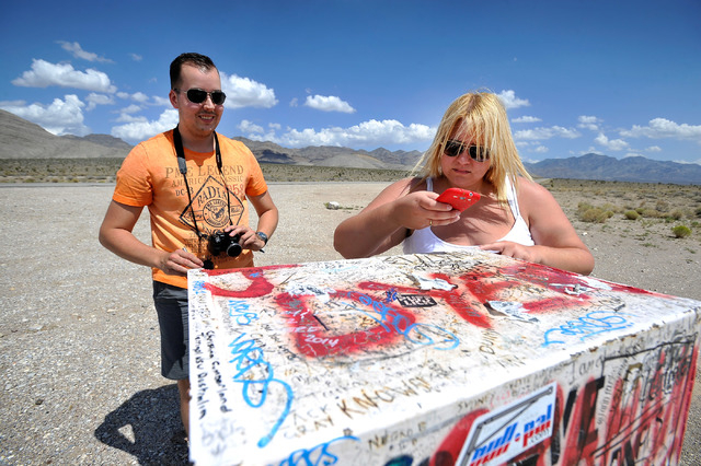 Floris Otten, left, of The Netherlands and Becky Cooper of England visit the famous black mailbox along Nevada Highway 375 on Tuesday, Aug. 5, 2014. The mailbox, which is now white and owned by a  ...
