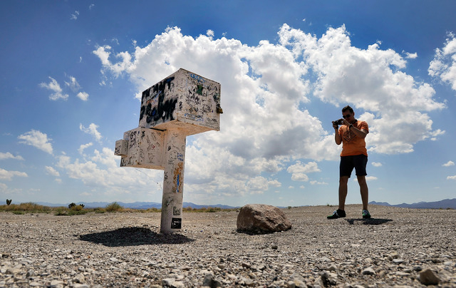 Floris Otten, of The Netherlands photographs the famous black mailbox along Nevada Highway 375 or Extraterrestrial Highway, on Tuesday, Aug. 5, 2014. The mailbox, which is now white and owned by a ...
