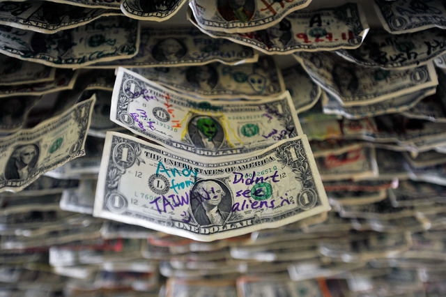 Messages on dollar bills are seen above the bar at the Little A'Le'Inn in Rachel, Nev. on Tuesday, Aug. 5, 2014. Visitors from around the globe stop at the little town of Rachel and visit the heav ...