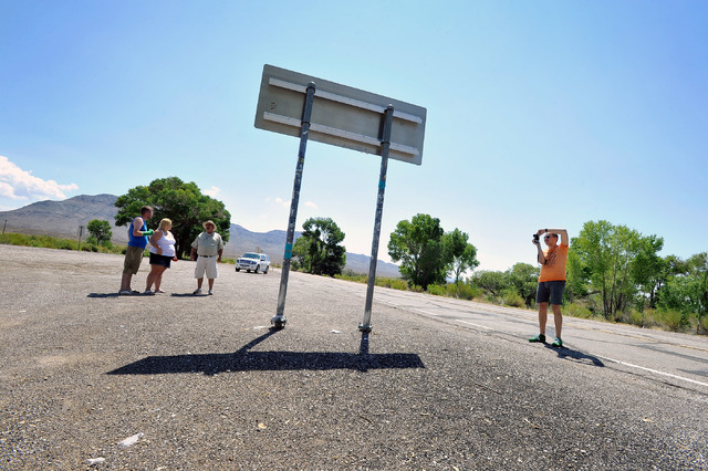 Tourist Floris Otten, right, of The Netherlands, snaps a photo of the Extraterrestrial Highway sign as he and other tourists, from left, Shane Cooper and his wife, Becky Cooper, of England, visite ...