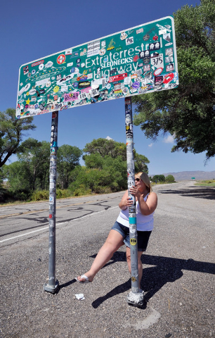 Becky Cooper, of England, dances on one of the poles holding the Extraterrestrial Highway sign on Tuesday, Aug. 5, 2014. Cooper was part of a small group that visited Rachel, Nev. and  other sites ...