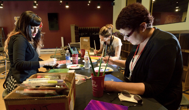 Artists and teachers, from left, Larissa Sweetland-Levings, Danielle Esposito and Melissa Brown work on paintings which will be used for decoration at Pinot's Palette in The District at Green Vall ...