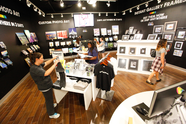 Jackie Peterson, left, and Benji Peterson, center, both of Indianapolis, look through items at Polaroid Fotobar at The Linq in Las Vegas on Wednesday, June 25, 2014. (Chase Stevens/Las Vegas Revie ...