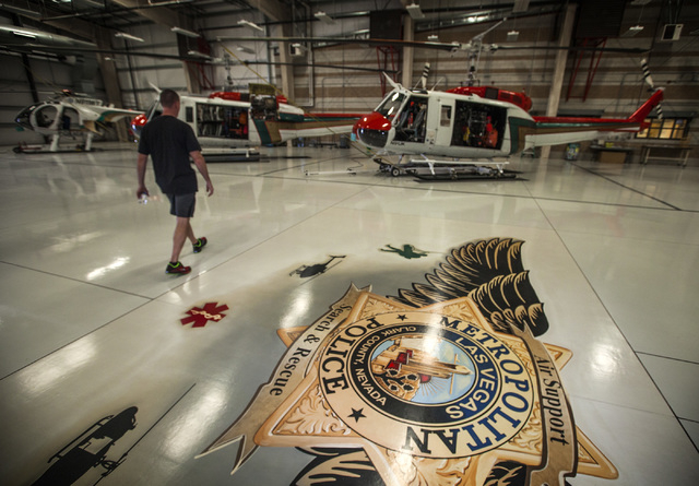 Search and Rescue Lt. Jack Clements walks toward two Vietnam-era Bell UH-1 Iroquois, commonly called a Huey,  in a hangar at the North Las Vegas Airport Friday, Aug 29, 2014 . Metro received helic ...