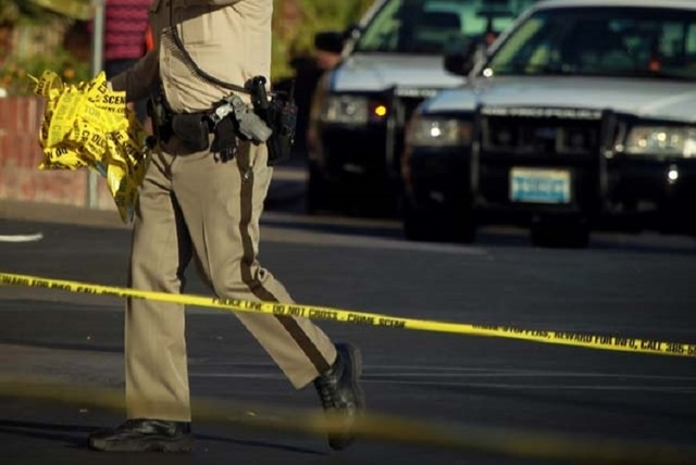 A Las Vegas police officer removes crime tape in this Monday, Oct. 29, 2012, file photo. (Jeff Scheid/Las Vegas Review-Journal)