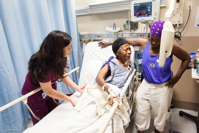 Emergency Department volunteer Heather Hudson, left, puts a pillow beneath patient Willie Jackson as daughter Michelle Jackson looks on at University Medical Center in Las Vegas on Tuesday, July 3 ...