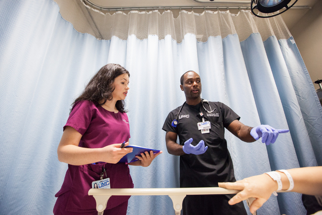 Emergency Department volunteer Heather Hudson, left, listens to Dr. Devon Moore as they see a patient at University Medical Center in Las Vegas on Tuesday, July 30, 2014. Hudson is an attorney who ...