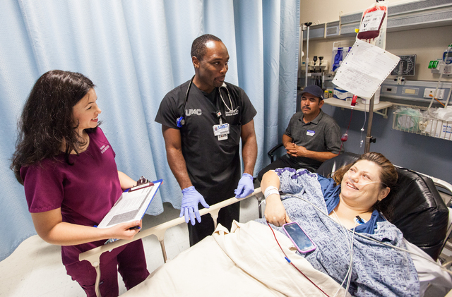 Emergency Department volunteer Heather Hudson, left, and Dr. Devon Moore, center, see patient Guadalupe Rodriguez, right, as relative Catalino Bahena (cq), second from right, looks on at Universit ...