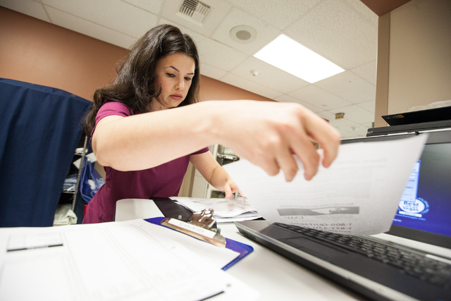 Emergency Department volunteer Heather Hudson prepares for her shift at University Medical Center in Las Vegas on Tuesday, July 30, 2014. Hudson is an attorney who has decided she wants to be a do ...
