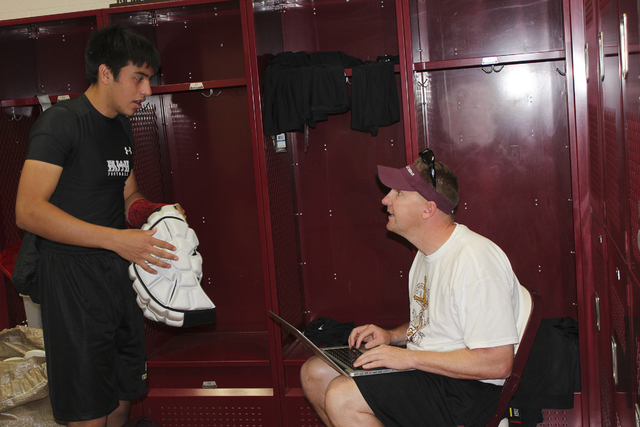 Senior linebacker Johnny Rodgers logs in his Guardian Cap, and other equipment, with Faith Lutheran assistant coach Jake Kothe.