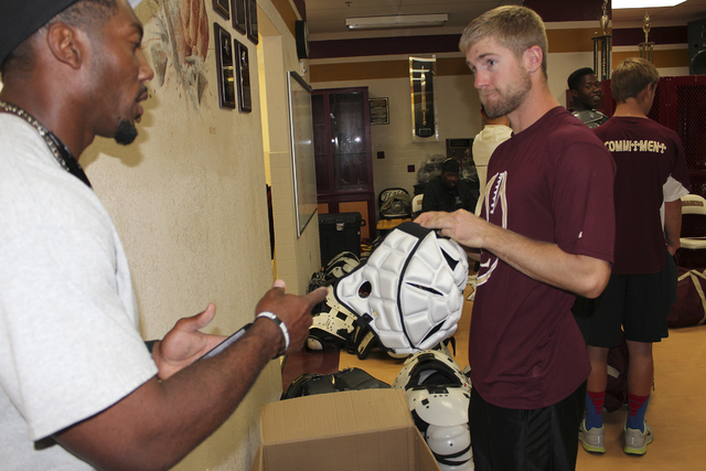 Faith Lutheran head coach Vernon Fox and assistant coach Grant Rolfsmeier chat while handing out equipment – including Guardian Caps – prior to the Crusaders leaving for football cam ...