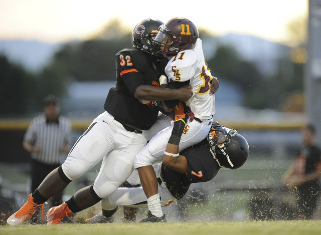 Chaparral Cowboys linebacker Antwain Allen (32) and defensive back Malachi Miles (7) tackle Eldorado Sun Devils wide receiver Demoreyah Holmes (7) in the first quarter high school football game at ...