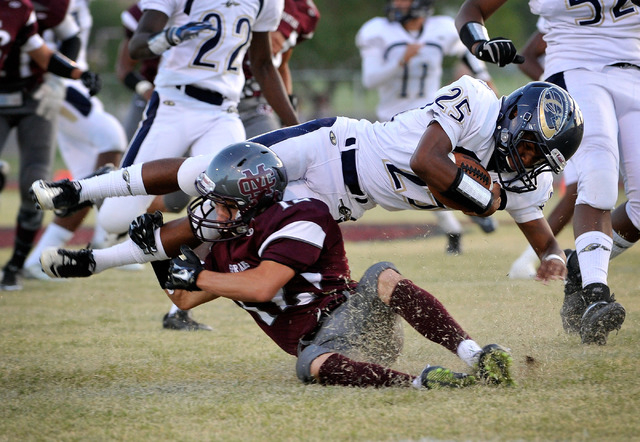 Cheyenne's Darius Haigler (25) is tripped up by Cimarron-Memorial's Stone Stevenson during a high school football game at Cimarron-Memorial High School on Friday, Aug. 29, 2014. (Photo by David Be ...