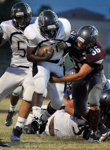 Cheyenne's David Walker tries to break free from Cimarron-Memorial's Nathaniel Garcia (36) during a high school football game at Cimarron-Memorial High School on Friday, Aug. 29, 2014. (Photo by D ...