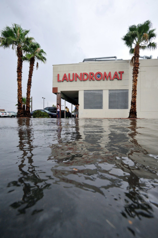 Flood waters strand people in front of a laundromat near on Montclair Street near Charleston Boulevard on Monday, Aug. 4, 2014. (Photo by David Becker/Las Vegas Review Journal)