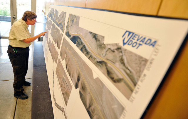 Kathy August, outdoor recreation planner for the Bureau of Land Management, reviews proposed road improvement plans during a public hearing at the Red Rock Canyon National Recreation Area visitor  ...