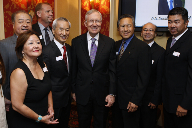 U.S. Sen. Harry Reid, D-Nev., center, takes photographs with members of the Asian Chamber of Commerce prior to taking the stage during their monthly lunch at the Gold Coast casino-hotel in Las Veg ...