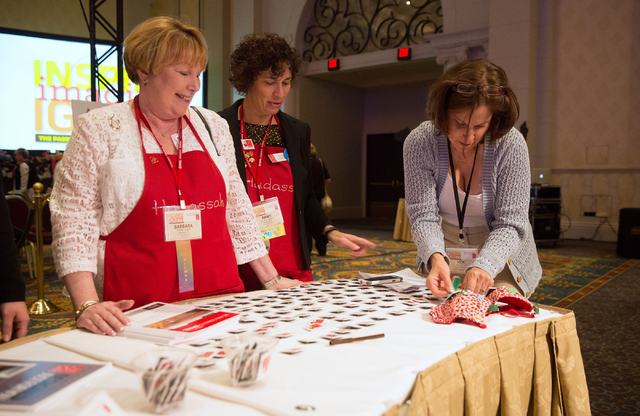 "Barbara Raben, left, and Randi Lampert (cq), center, watch as Vicki de Groot (cq) decorates a bra for ""The Uplift Project"" during the Hadassah National Convention at The Venetian on Wednesday, Jul ..."
