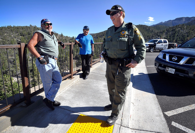 Las Vegas police Sgt. Andy LeGrow, right, greets tourists Dominic Piciotta, left, and Ron Pisciotta as he patrols the Desert View Overlook along state Route 158 on Tuesday, Aug. 26, 2014. LeGrow l ...