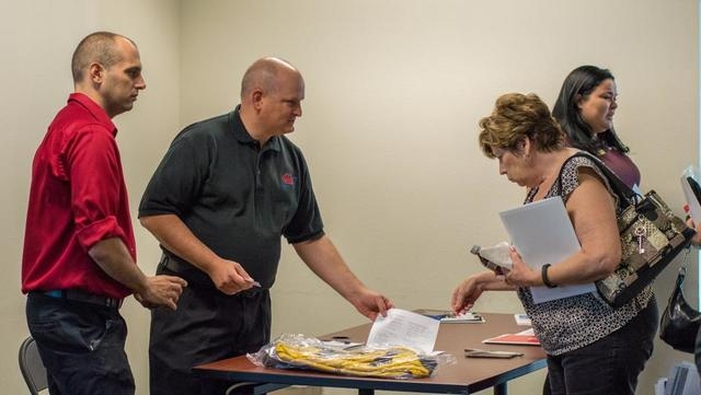 American Red Cross employee Nathaniel Montgomery, left, and AAA employee James Miller, center, man a table at a Ready, Set, Respond! workshop Aug. 7 at the Paseo Verde Library, 280 S. Green Valley ...