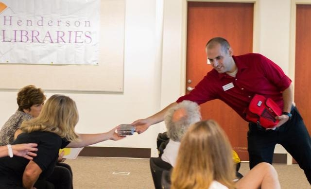 American Red Cross employee Nathaniel Montgomery hands Las Vegas resident Sharen Black packaged food at a Ready, Set, Respond! workshop Aug. 7 at the Paseo Verde Library. (Fernando Lopez/Special t ...