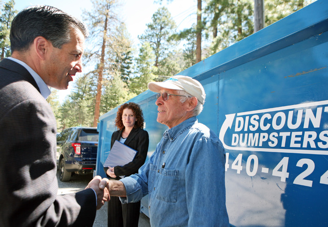 Gov. Brian Sandoval, left, visits with resident Rodney Dukkes after speaking at a news conference at the Rainbow Canyon subdivision at Mount Charleston Monday, Aug. 25, 2014, near Las Vegas.  Sand ...