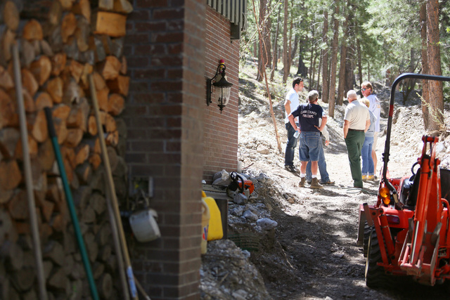 People stand in a ravine that was caused by flooding near the Grismanauskas home in the Rainbow Canyon subdivision at Mount Charleston Monday, Aug. 25, 2014, near Las Vegas. The Grismanauskas fami ...